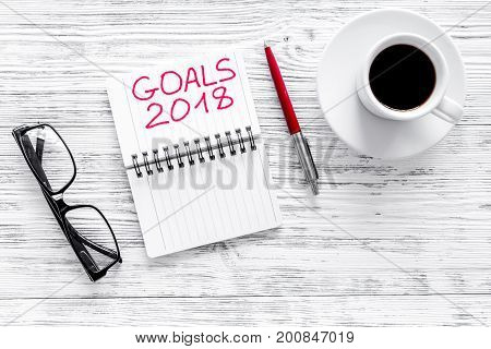 Set a goal for new year. Notebook near pen and cup of coffee on grey wooden background top view.