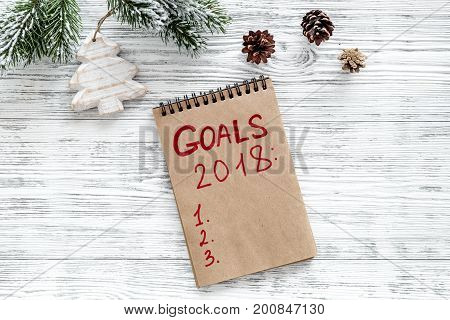Make a goals list for 2018. Notebook and christmas decoration on wooden background top view.