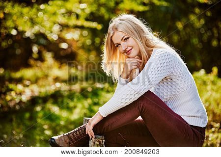 Beautiful smiling woman sitting on fence in autumn garden