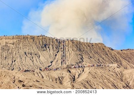 Many tourists walking to crater of Bromo volcano close-up with erupting smoke in Bromo Tengger Semeru National Park East Java Indonesia.