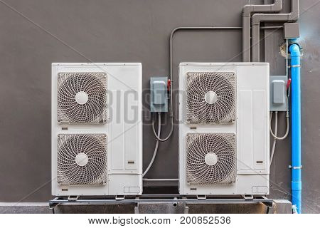 Air conditioning compressor installation on pedestal, Gray wall