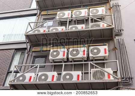 Group of compressors of air conditioner hanging on the grey wall.