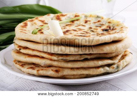 Khychiny - traditional caucasian flatbread filled with сheese and herbs.  Flat bread stuffed with feta and wild garlic.