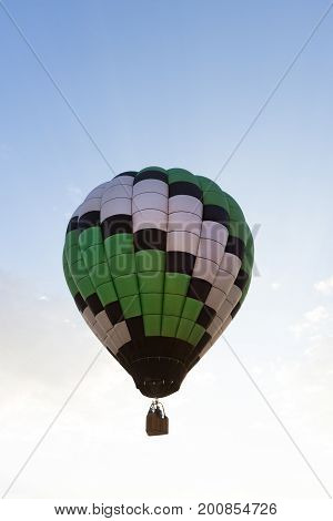 A green, white and black hot air balloon in flight with several passengers in the basket. The wicker basket carrying passengers is in silhouette.