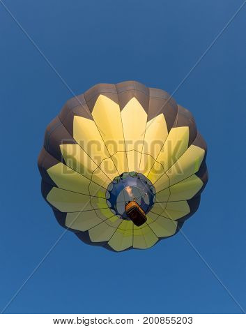 A yellow and black hot air balloon in flight. The flame is seen above the wicker basket carrying passengers. The deep blue sky is cloudless. Photographed from below. Image has copy space.