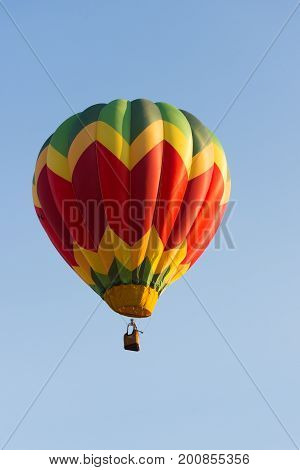 A yellow red and green hot air balloon in flight. A wicker basket carries passengers. The light blue sky in the background is cloudless. The colors have a chevron pattern.