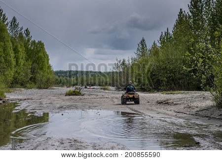 Dad and son riding their ATV through water and sand
