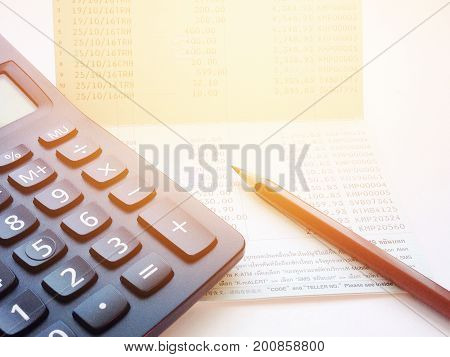 Business, finance, savings or loan concept : Calculator and pencil on saving account passbook or financial statement