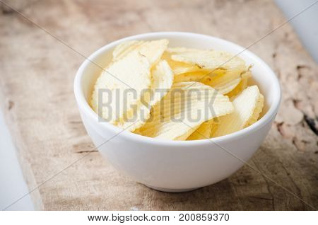 Potato chips in a bowl on wooden background for eating,crunchy snack