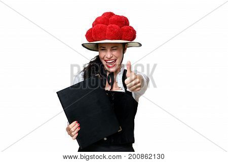Enthusiastic laughing young Black Forest waitress wearing a tradition bollenhut with red pompoms giving a thumbs up gesture of approval isolated on white