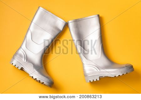 Pair of marching stylish silver gumboots on orange background. Autumn creative background Top view. Flat lay.