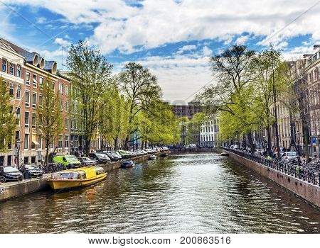 AMSTERDAM, NETHERLANDS - MARCH 30, 2017  Boats Reflection Bicycles Canal Amsterdam Holland Netherlands. Canals in Amsterdam in Early Spring.