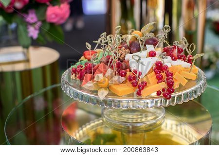Close-up of sweet delicious snacks served on glass stand on table for catering.