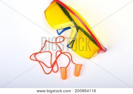 Orange earplug and safety glasses for work. Earplug to reduce noise on a white background