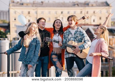 Student music group at festival. Creative get-together outdoors, young company of people with guitar