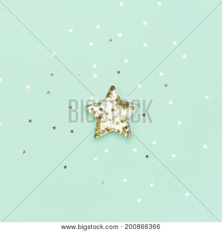 Christmas star made with mold for the cookies and gold sparkling stars on green background. Flat lay. Holidays and Christmas concept