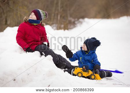 Portrait of cute little toddler sitting on snow and playing with his yellow tractor toy in the park together with his brother. Children playing outdoors. Lifestyle concept