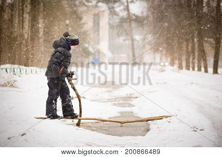 Portrait of cute kid boy with wooden stick trying to cross big puddle on a winter day. Child walking ourdoors and exploring nature. Lifestyle concept