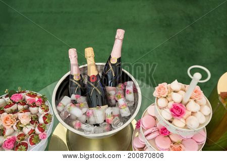 From above shot of table with served sweet snacks and bottles of champagne in wine cooler.