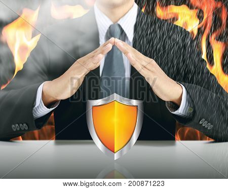 businessman and shield with fire background, insurance concept