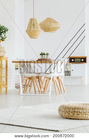 Modern table with four white chairs in cosily dining room