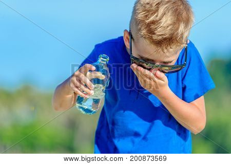 Portrait Of A Thirsty Handsome Boy In Sunglasses Drinking Water On The Desert Tropical Beach