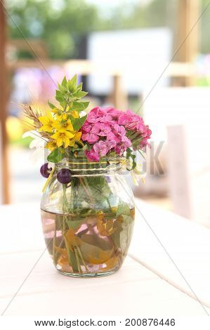 Bouquet of spring colorful flowers in a vase. Romantic floral still life with bouquet of daisy grape hyacinth and cowslip flowers in a vase. Fine art flower photography.