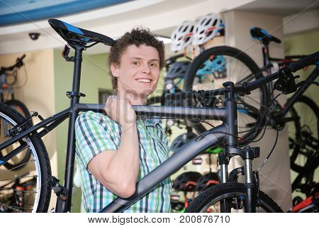 Young man holding bicycle in shop