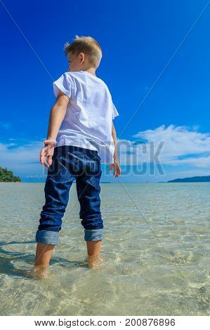 Eight Years Old Boy Walking On Crystal Clear Water, Back View