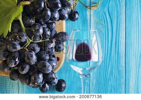 Grapes and wine glass on a blue wooden table top view. Branch of fresh ripe red grapes. Beautiful background with a branch of blue grapes. Dark red wine grapes.