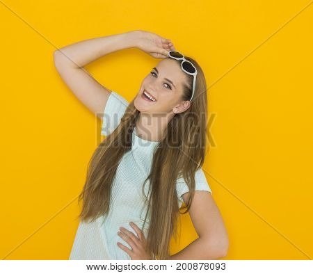 Colorful portrait of young attractive woman wearing sunglasses in hearts form and say hey or wow. Summer beauty concept on orange background