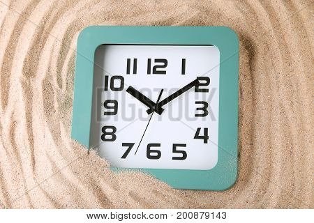 New green clock on the beach sand