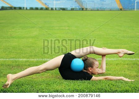 Young Girl Gymnast With Ball On Green Grass