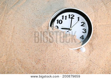 New black clock in the beach sand