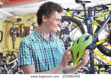Young man choosing bicycle helmet in shop