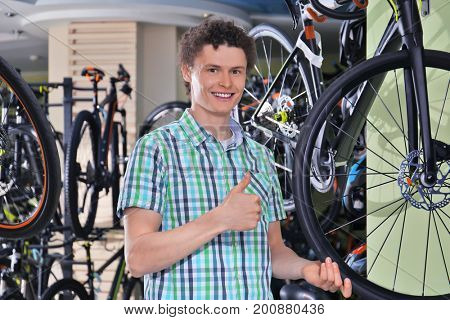 Young man choosing bicycle in shop