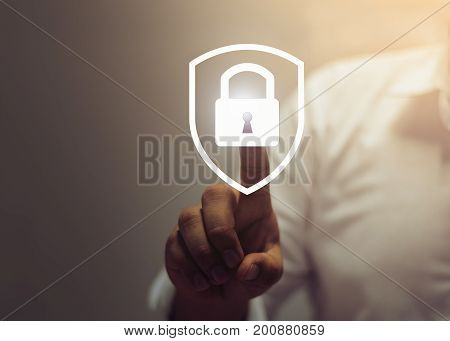 Person touching a shield with a lock symbol, concept about security, cybersecurity and protection against dangers