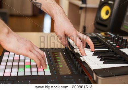 Producer makes a music on MIDI keyboard