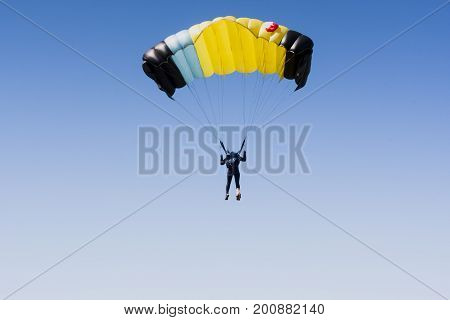 Skydiver in clean sky with copy space. Yellow parachute