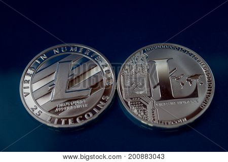 On a blue background are two coins - It's the back and face of the coin of a fictitious crypto currency Litecoin.