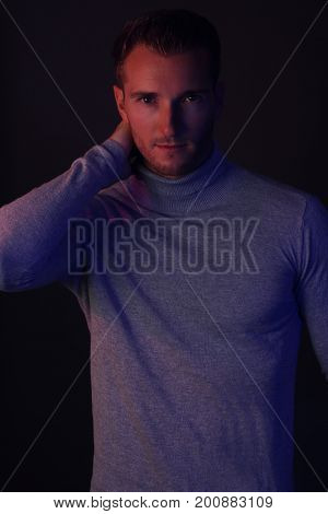 Winter fashion for men . Handsome man wearing a turtleneck on a gray background