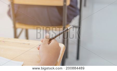Blurred of Asian students hand holding pen for writing Exams paper sheet or test papers on row wood desk table with student uniform in exam class room education concept