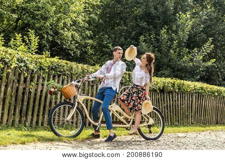 Young couple with bike tandem in park. Young people keep hats in their hands and smile. On the back of the tree fence.