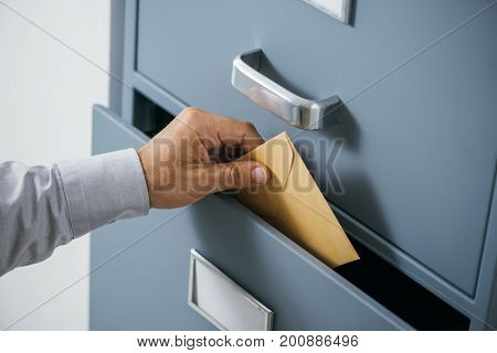 Businessman Putting An Envelope Into A Drawer