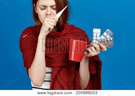 Beautiful woman on a blue background holds a mug, pills, thermometer, sickness, sick, flu.