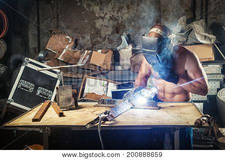 Man Welding A Metal With Arc Welding Machine