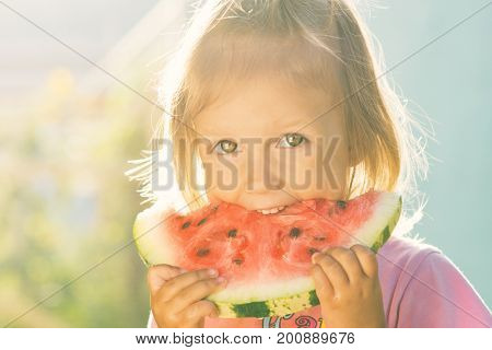 Portrait of a little girl with big beautiful eyes eating a watermelon