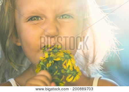 Portrait of a child of a little girl with big beautiful eyes sniffing flowers and wrinkling a nose