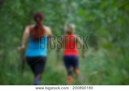 Blurred photo from back of two athletes running in woods at summermorning