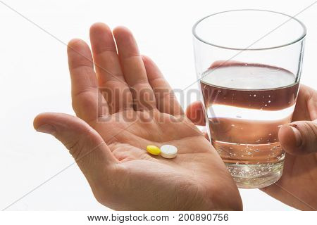 Two Tablets In The Hand And A Glass Of Water